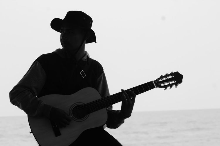 Man playing guitar at sea against sky