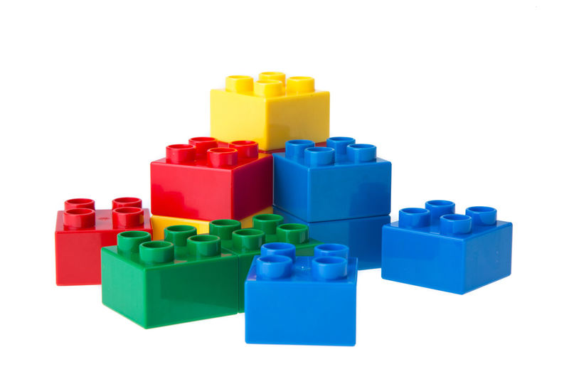 Stack of multi colored toy blocks against white background