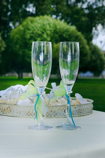 Close-Up Of Wine Glasses On Table Against Trees