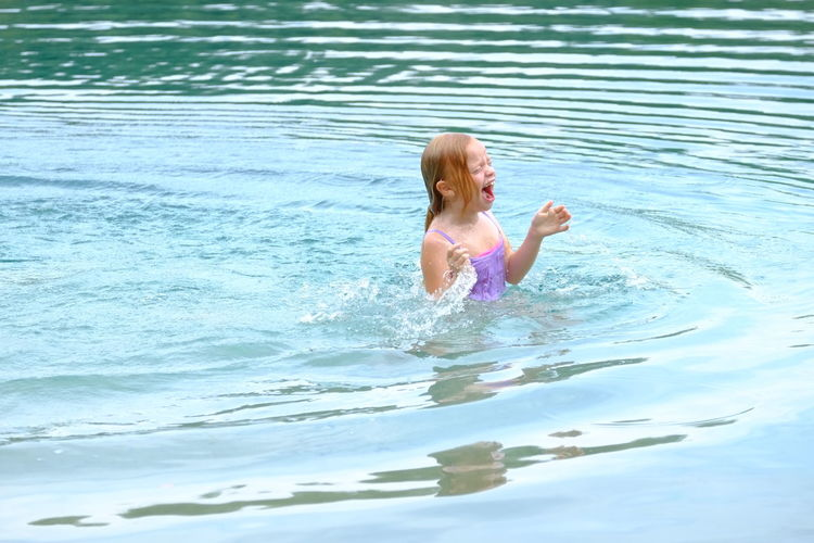 Little girl swimming in open blue natural water in the summertime Child Childhood Day Enjoyment Fun Holiday Innocence Leisure Activity Lifestyles Nature One Person Outdoors Pool Real People Smiling Swimming Swimming Pool Swimwear Water Waterfront