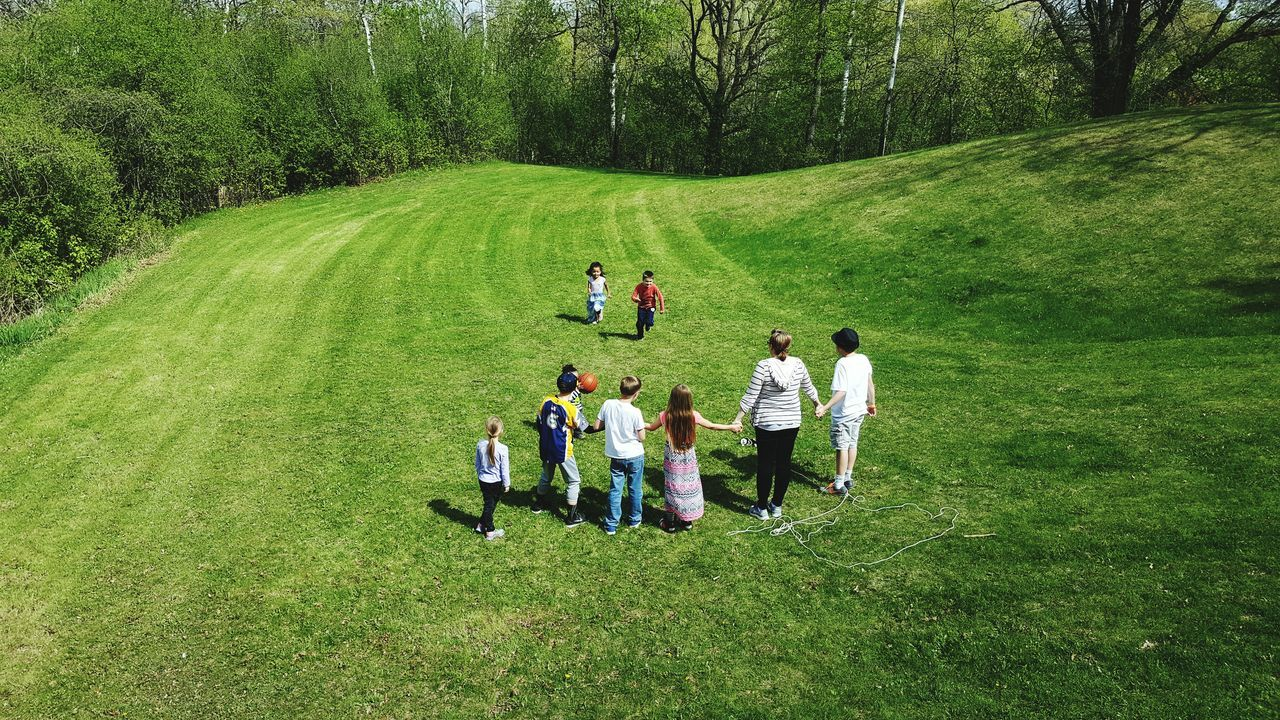 real people, grass, tree, medium group of people, togetherness, field, men, growth, standing, nature, casual clothing, green color, high angle view, women, leisure activity, day, lifestyles, teamwork, outdoors, friendship, beauty in nature, young adult, adult, people