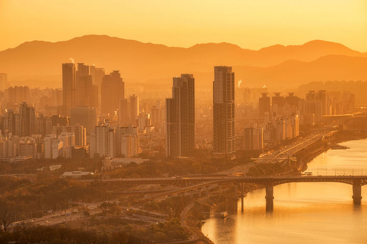 orning sunrise in Seoul and views of the Han River in South Korea. Architecture Bridge; Korea; River; Seoul; City; South; Hangang; Skyline; Cityscape; Night; View; Han; Sky; Urban; Building Exterior Built Structure City Cityscape Dawn Day Landmark; Travel; Landscape; Building; Scene; Asia; Tower; Architecture; Dongjak; Business; Dark; Mountain; Downtown; Twilight; Blue; Traffic; Light; Modern Mountain Nature No People Outdoors Sky Skyscraper Sunset Travel Destinations Urban Skyline Water Waterfront