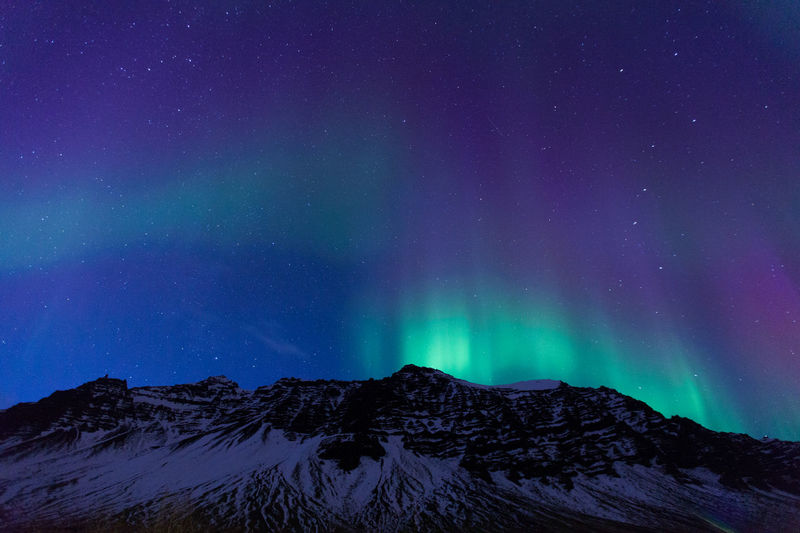 Low Angle View Of Aurora Borealis Over Snowcapped Mountains At Night