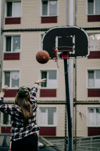 Rear view of woman playing basketball