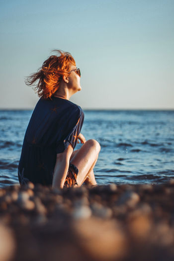 Rear view of girl sitting on beach against sky