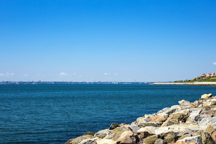 Scenic view of sea against clear blue sky