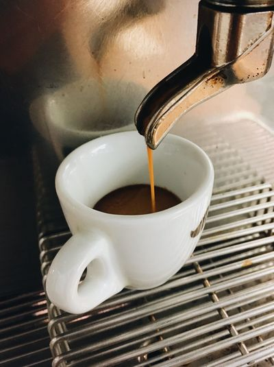 Close-up of coffee dripping down into espresso cup