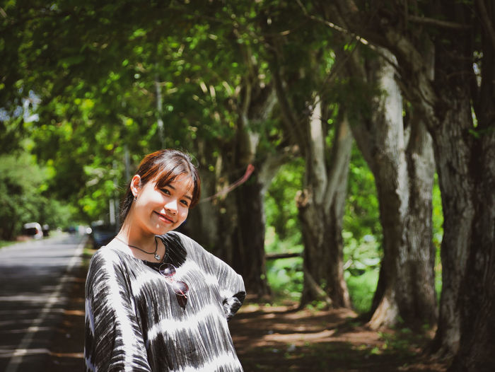 Portrait of smiling young woman standing against trees