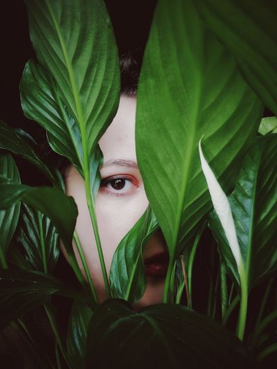 Close-up portrait of young woman seen through plants