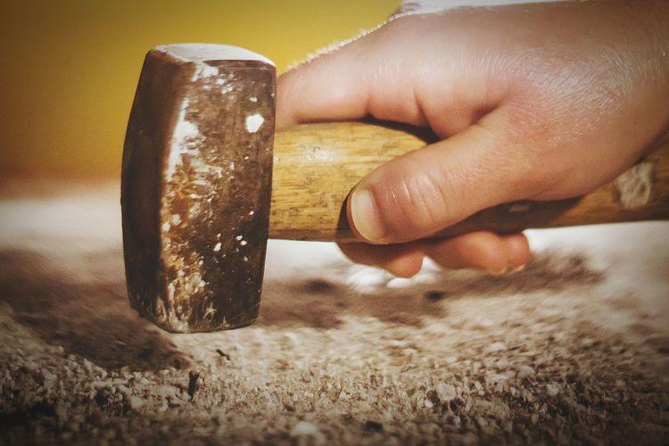 Close-up of person hammering nail