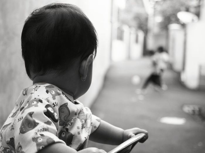 Close-Up Of Toddler On Chair Looking At Street In Town