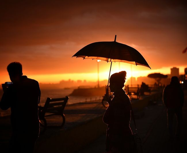 Silhouette woman holding umbrella while standing in street against cloudy sky