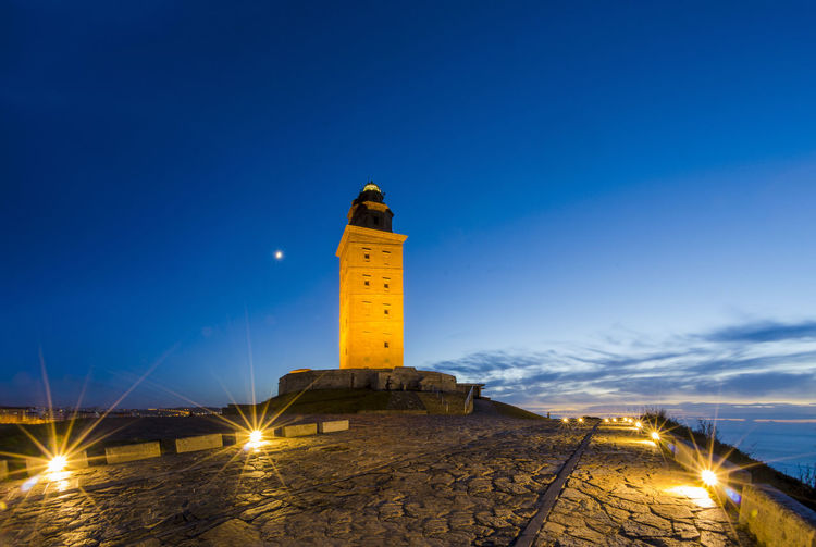 Tower of Hercules, at night, the almost 1900 years old and rehabilitated in 1791 55 metres tall structure is the oldest Roman lighthouse in use today and overlooks the Atlantic coast of Spain from A Coruna. Antique Atlantic Ocean Coruña Galicia Spain Hercules SPAIN Architectual Image Architecture Building Exterior Built Structure Coast Illuminated Lighthouse Long Exposure Moon Night No People Old Old Buildings Roman Sea Sky Sunset Tourism Tower
