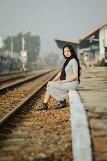 Portrait of woman on railroad tracks