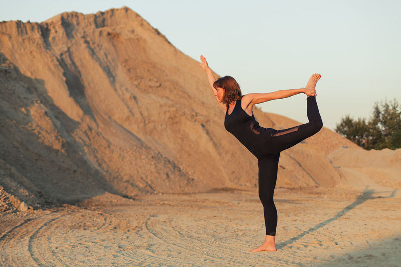 lord of dance yoga pose Full Length Lifestyles Leisure Activity Healthy Lifestyle Exercising Young Adult Women Wellbeing Balance Day Nature Sport Yoga Flexibility Skill  Human Arm Outdoors Leg Sandy Background Care Fit Workout Natarajasana barefoot Recreation
