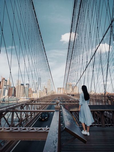 Rear View Of Woman Standing On Suspension Bridge Against Sky
