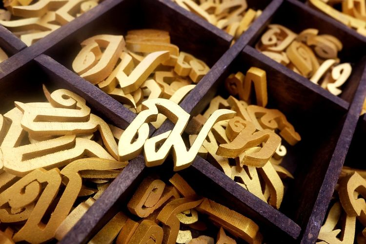 Close-up of various wooden alphabets in containers