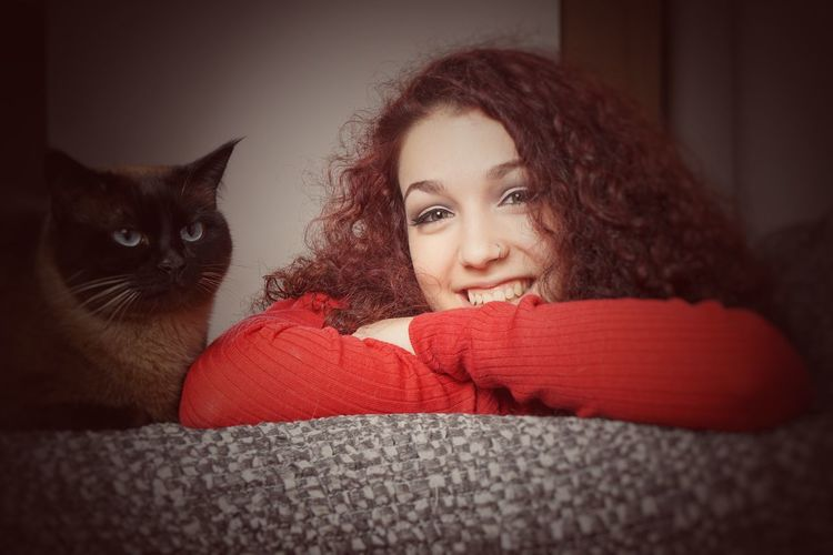 Portrait of smiling woman with cat on couch at home