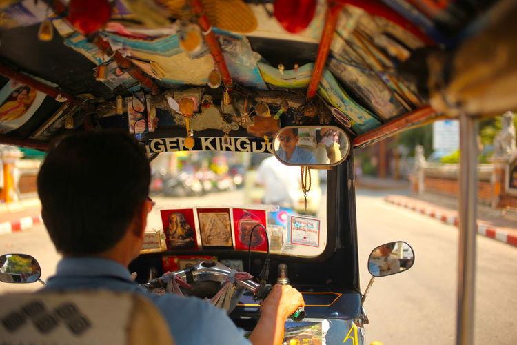 Rear view of tuk tuk driver with passenger