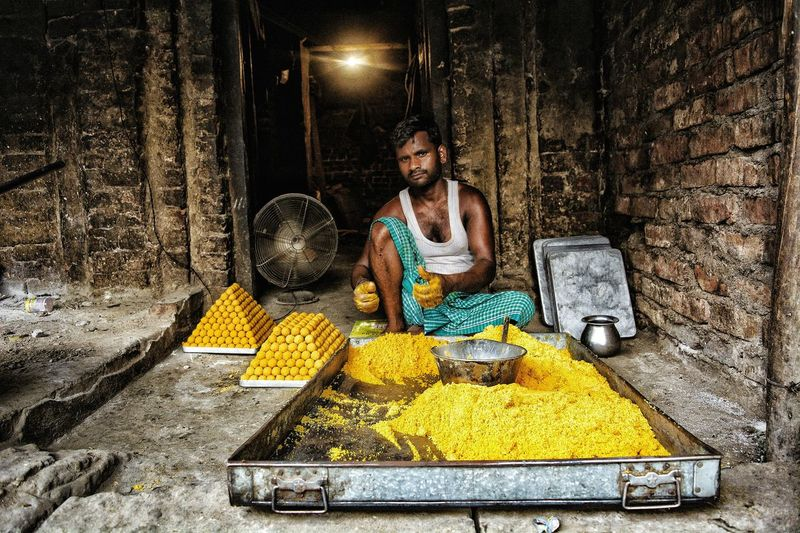Portrait of mid adult man making sweet food while sitting at workshop