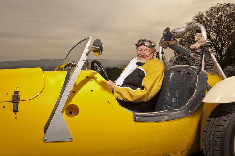 Portrait of smiling man sitting on yellow cart