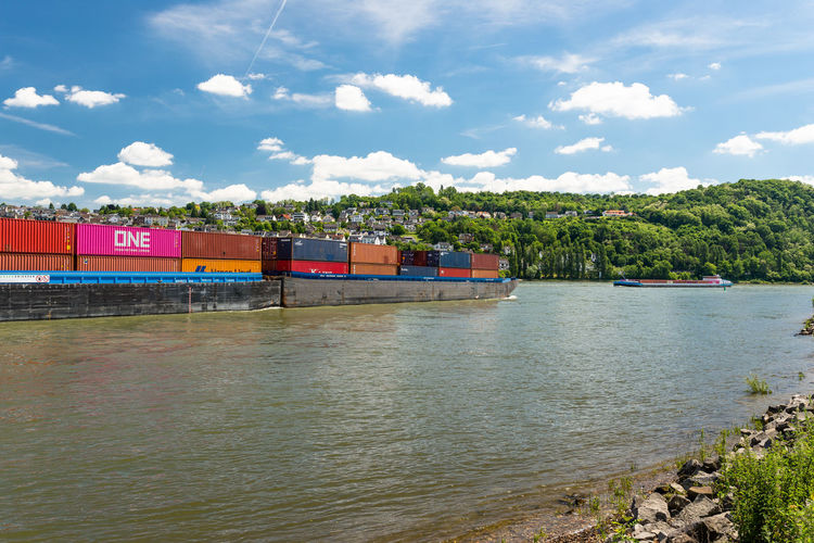 Two connected barges carrying a lot of containers on the rhine river in western germany in koblenz.