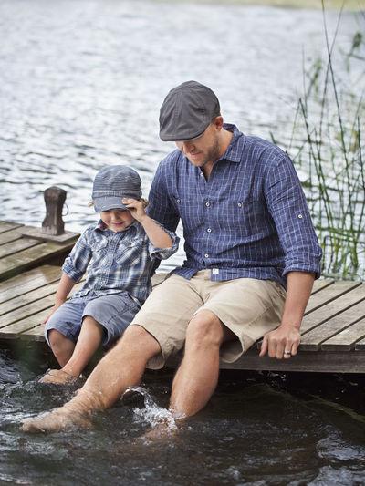 Young man sitting on lake