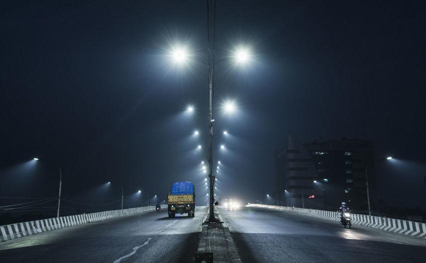 Cars on illuminated road in city at night