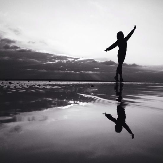 Silhouette of woman jumping in sea