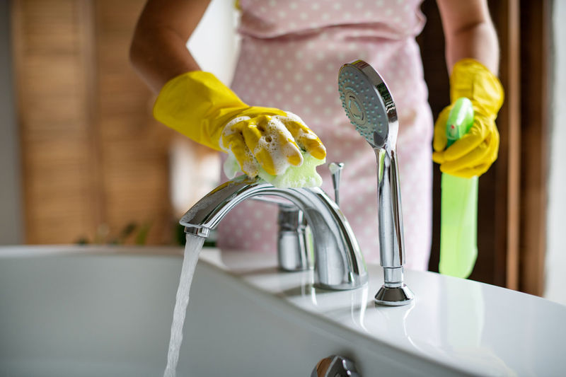 Midsection of woman pouring water from faucet
