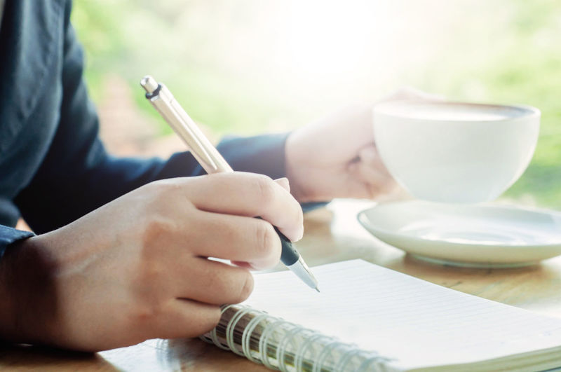 Midsection of man having coffee while writing on spiral notebook at table in cafe