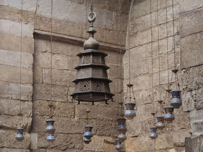 Mamluk metalwork lantern surrounded by blown glass calligraphic lamps in the Madrasa of Sultan Barquq, Cairo. Architecture Built Structure Cairo# Egypt# Glass Lamp# Hanging Lantern# Metalwork# Mosque# Place Of Worship