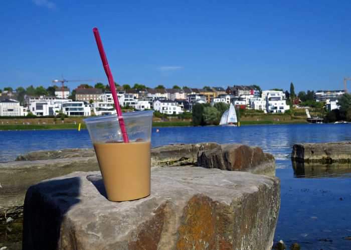 Architecture Beverage Chilling In The Sun Coffee Dortmund Drink Food And Drink Freshness Harbor Iced Coffee Iced Latte In Front Of Lake Lake View Lakeshore Lakeside Latte Macchiato Phoenixsee Refreshing Drink Relaxing Sailing Sailing Boat Sea Straw Water