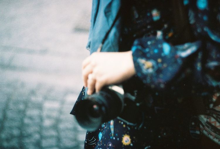 Midsection of woman photographing at camera