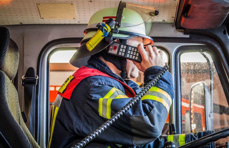 Firefighter Taking Emergency Call In Firetruck