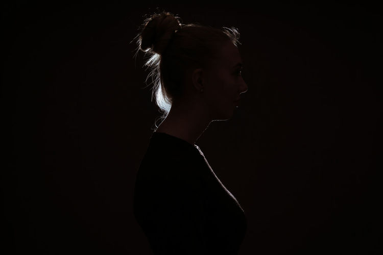One Person Studio Shot Women Girl People Young Woman Black Background Side View Young Adult Copy Space Profile View Dark Mystery Rim Light Silhouette Identity Hair Bun Back Lit