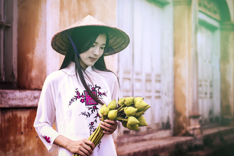 Vietnamese woman in traditional clothing holding flowers