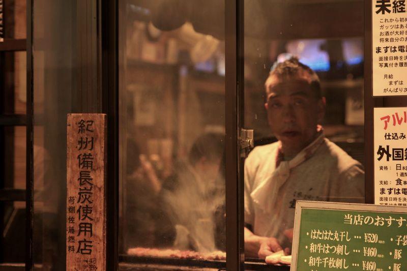 Portrait of man looking through glass window