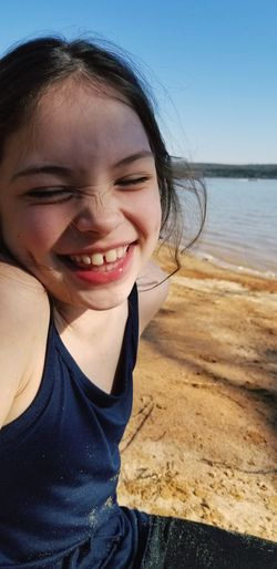 Cheerful girl sitting at beach