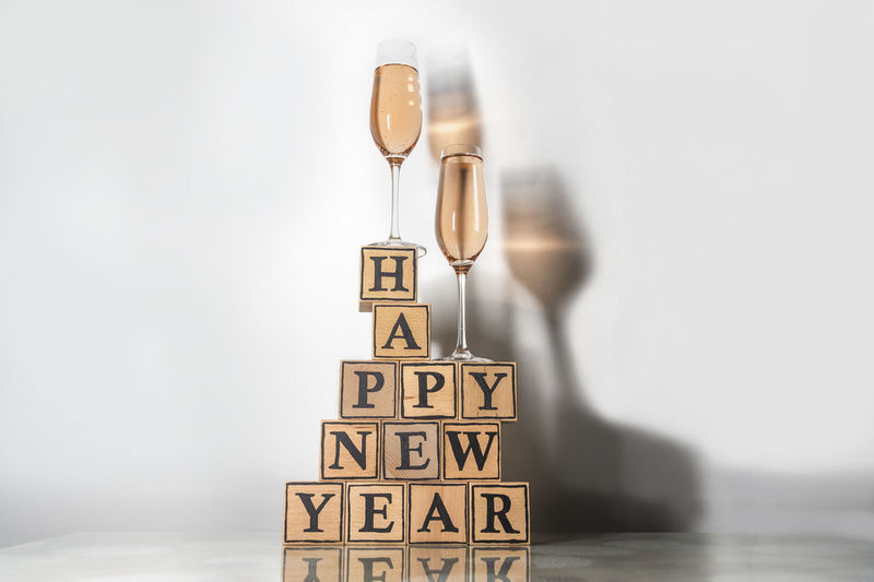 Glasses with Rosy champagne make a colored shadow and wooden cubes form the text happy new year Bright Celebration Champagne Champagne Glasses Copy Space Glasses Greeting Letters New Year's Eve Stack Text Alcohol Balance Concept Happy New Year Letter Cube Message Party Pink Colored Rosy Shadow Still Life Studio Shot White Background Wood - Material Food Stories
