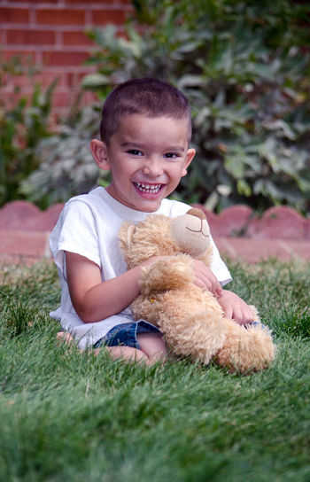 A laughing young boy sits in the grass with his favorite stuffed bear toy Bear Hanging Out Love Boy Childhood Cute Day Ethnic Favorite Toy Friendship Grass Happiness Hispanic Kid Laughter Nature One Person Outdoors Person Portrait Real People Smiling Teddy Bear The Portraitist - 2018 EyeEm Awards