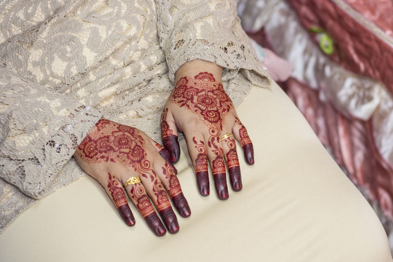 Midsection Of Bride With Henna Tattoo On Hands