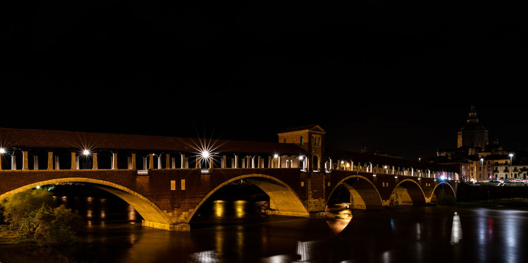 Illuminated bridge over river by buildings against sky at night in pavia, italy