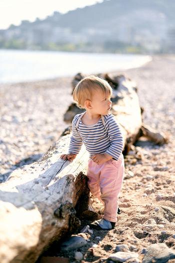 Cute boy standing on rock