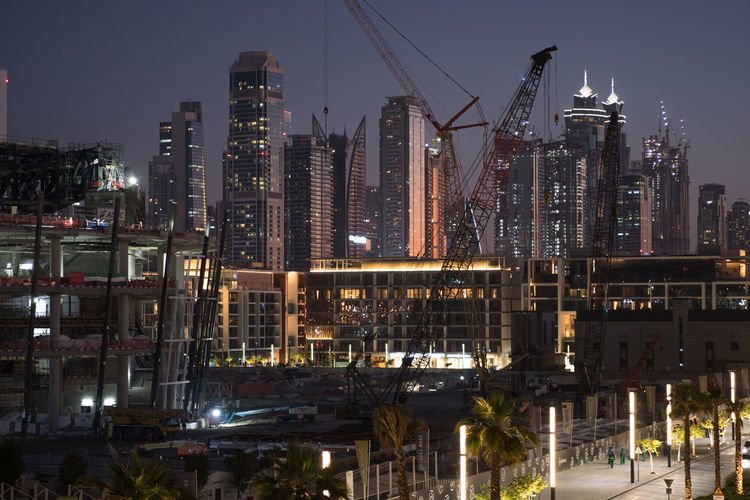 Illuminated buildings and cranes in city at night