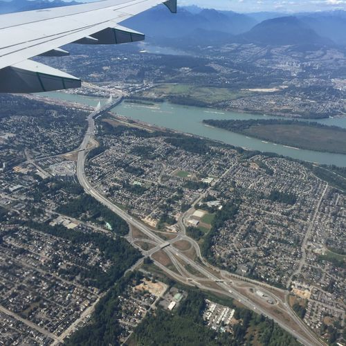 Cropped Image Of Airplane Flying Over Human Settlement By River