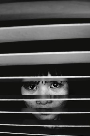 Portrait Of Woman Seen Through Blinds