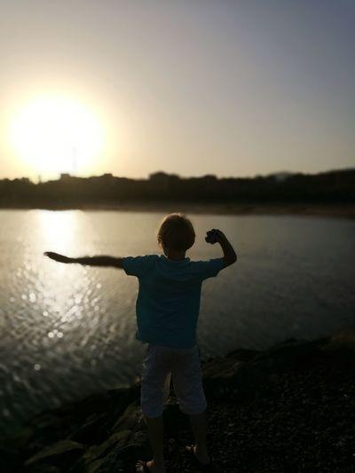 Water Child Full Length Sunset Standing Lake Rear View Silhouette Reflection Sky Horizon Over Water Calm Beach Sandy Beach Sand Seascape Shore Coast Children Ocean