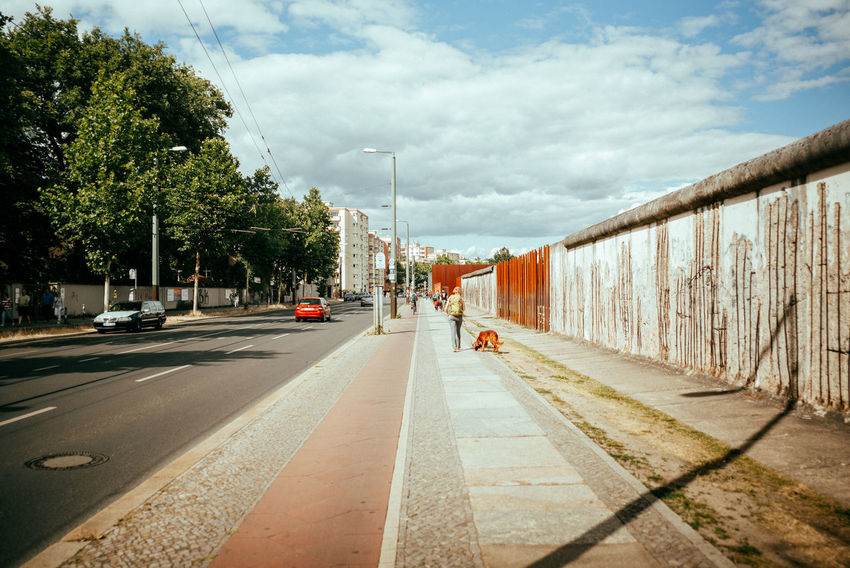 Berlin Wall City Historical Monuments Historical Sights Memorial The Street Photographer - 2018 EyeEm Awards The Traveler - 2018 EyeEm Awards Architecture Built Structure Car City Cloud - Sky Day Direction History Motor Vehicle No People Outdoors Plant Road Sky Street Streetphotography The Way Forward Urban Urban Skyline