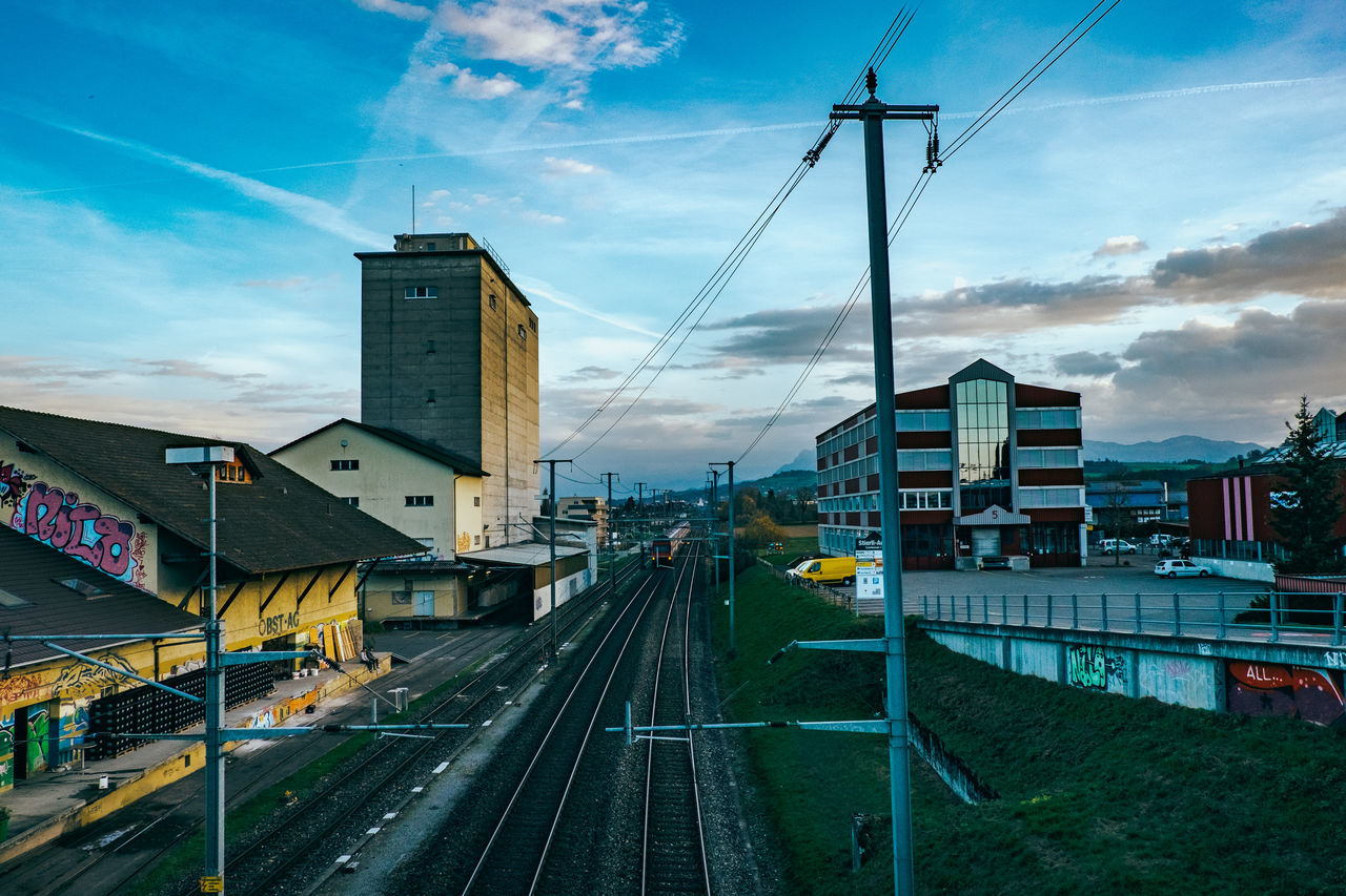 sky, transportation, cloud - sky, building exterior, built structure, architecture, railroad track, cable, rail transportation, power line, electricity pylon, connection, mode of transport, outdoors, city, day, no people, road